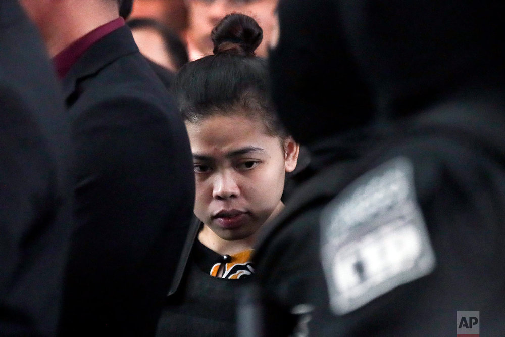 Indonesian Siti Aisyah, center, is escorted by police at Kuala Lumpur International Airport in Sepang, Malaysia, Tuesday, Oct. 24, 2017. The two women accused of killing Kim Jong Nam, the North Korean leader's half brother, toured the Malaysian airport Tuesday as participants in their murder trial visited the scene of the attack. (AP Photo/Sadiq Asyraf)