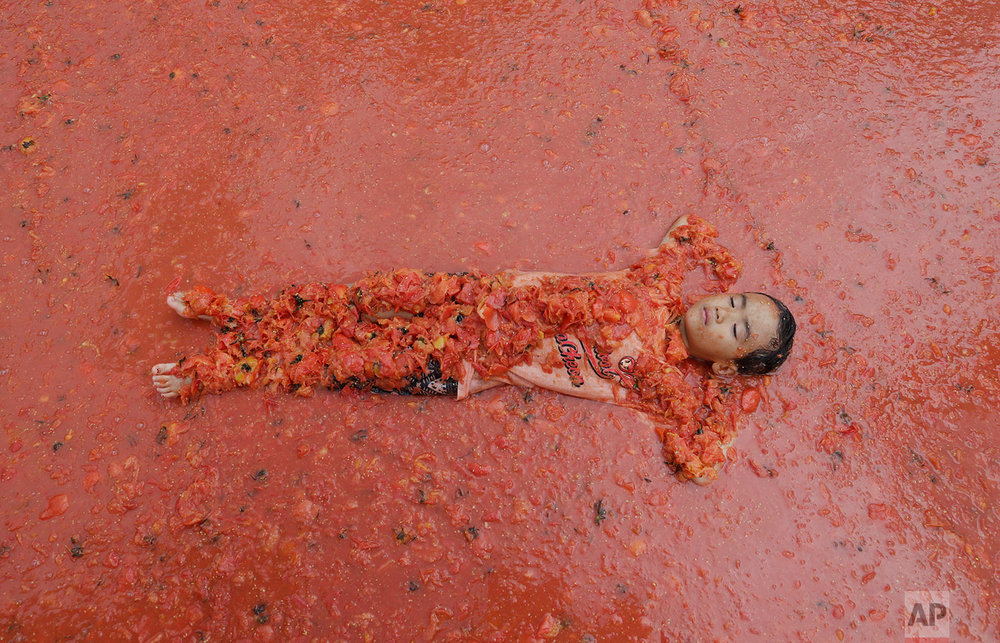 A boy lies in a pool of tomatoes during the 2017 Tomato Festival in Hwacheon, South Korea, Saturday, Aug. 5, 2017. The festival runs from Aug. 4 to Aug. 7. (AP Photo/Ahn Young-joon)