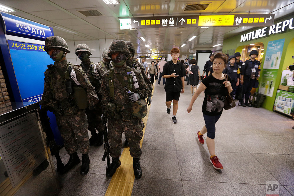 "Passengers walk past South Korean army soldiers during an anti-terror drill as part of Ulchi Freedom Guardian exercise, at a subway station in Seoul, South Korea, Tuesday, Aug. 22, 2017. As North Korea vowed ""merciless retaliation"" against U.S.-South Korean military drills it claims are an invasion rehearsal, senior U.S. military commanders on Tuesday dismissed calls to pause or downsize exercises they called crucial to countering a clear threat from Pyongyang. (AP Photo/Ahn Young-joon)"