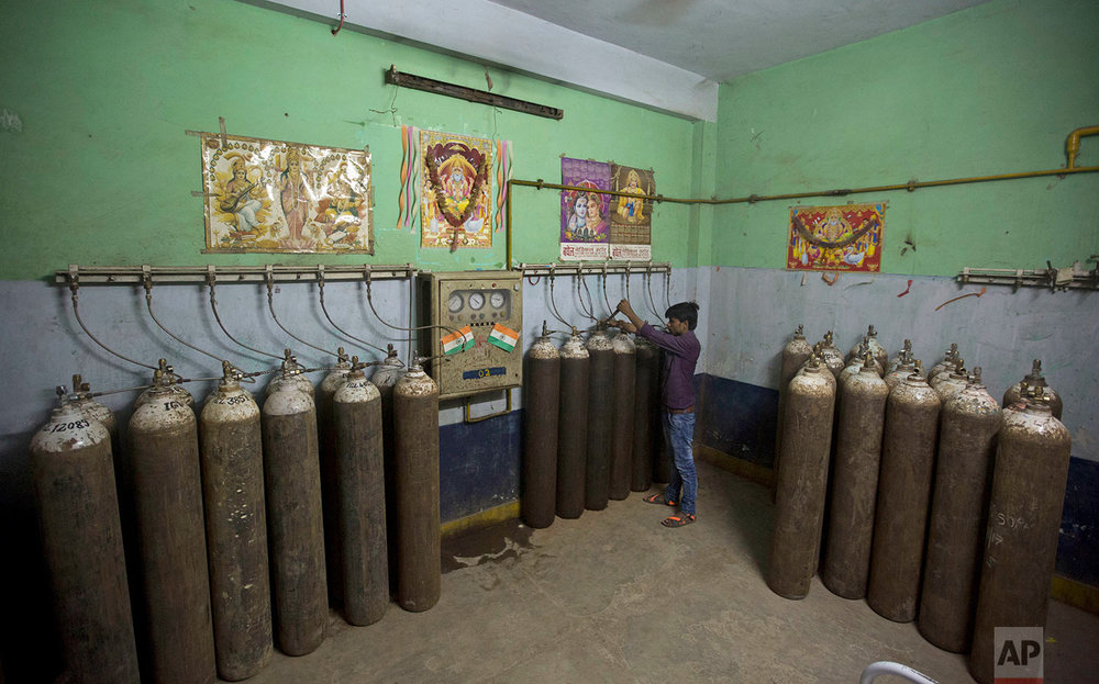 A hospital staff member checks newly arrived oxygen cylinders at Baba Raghav Das Medical College Hospital in Gorakhpur, in the northern Indian state of Uttar Pradesh, Saturday, Aug. 12, 2017. Parents of at least 35 children who have died in the state-run hospital over the past three days have alleged that the fatalities were due to the lack of a sufficient oxygen supply in the children's ward. District Magistrate Rajiv Rautela said Saturday that the deaths of the children being treated for different ailments were due to natural causes. He denied that an insufficient oxygen supply led to their deaths. (AP Photo/Rajesh Kumar Singh)