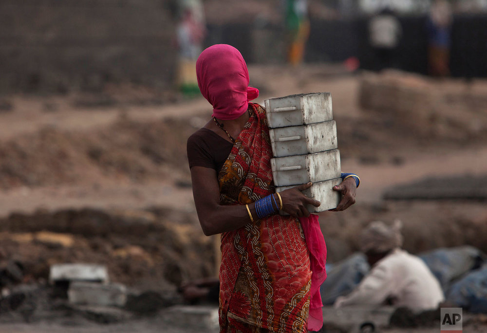 An Indian woman reacts to camera as she works at a brick kiln with her face covered to protect from dust on the eve of International Women's Day in Hyderabad, India, Tuesday, March 7, 2017. (AP Photo /Mahesh Kumar A.)