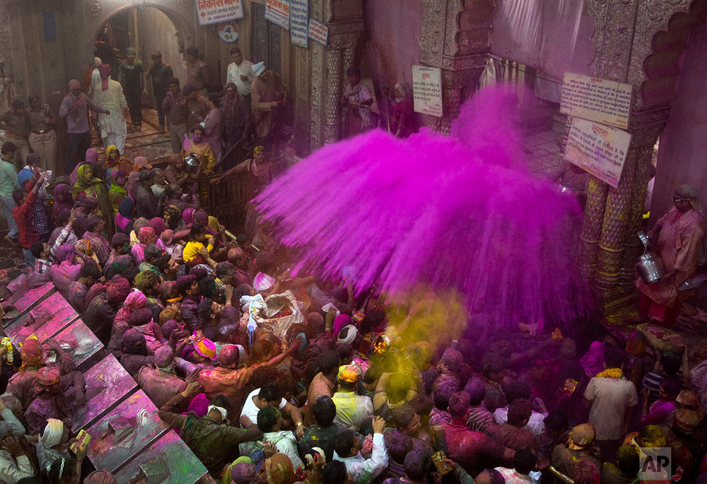 Hindu priests throw color powders at the devotees inside Banke Bihari temple, dedicated to Lord Krishna, during Holi festival celebrations in Vrindavan, India, Wednesday, March 8, 2017. Holi, the festival of colors, celebrates the arrival of spring. (AP Photo/Manish Swarup)