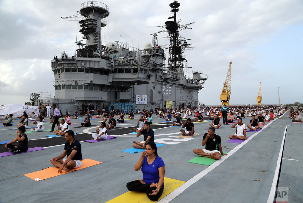 Indian armed forces and their families members perform Yoga on the deck of the Indian Naval aircraft carrier Viraat to mark International Yoga Day in Mumbai, India, Wednesday, June 21, 2017. Yoga practitioners took a relaxing break to bend, twist and pose Wednesday morning for the annual event celebrating the practice, especially in the country where it began. (AP Photo/Rajanish Kakade)