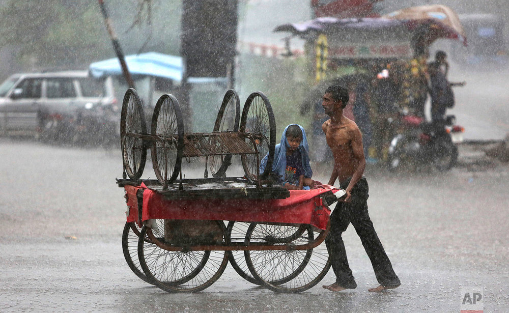 An Indian man tries to protect his child from the pelting rain by covering him with his shirt as he pushes a handcart in Jammu, India, Wednesday, July 12, 2017. The monsoon season in India lasts from June to September is very crucial for India's agriculture sector that accounts for more than 13 percent of the economy and provides work for about half of the country's 1.25 billion people. (AP Photo/Channi Anand)