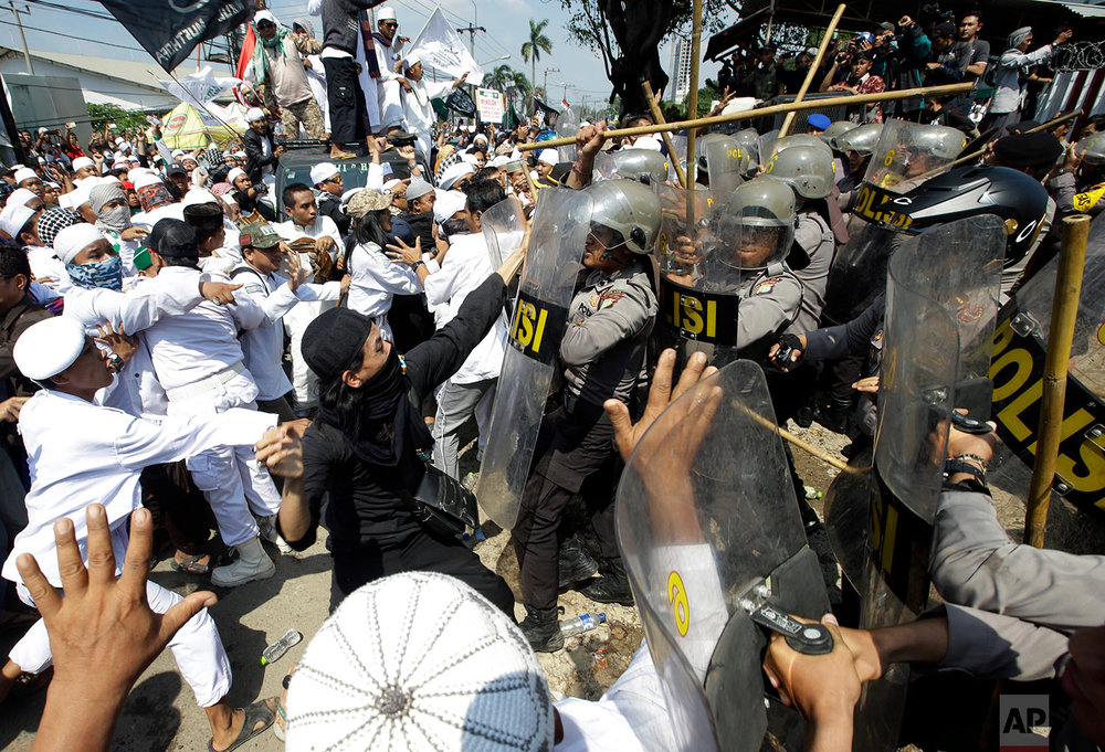 In this Friday, March 24, 2017 photo, police officers clash with Muslim hardliners during a protest against the construction of a Catholic church in Bekasi, Indonesia. Indonesian police fired tear gas to disperse the protesters as they tried to force their way into the Santa Clara church, which has been under construction since November. (AP Photo/Achmad Ibrahim)