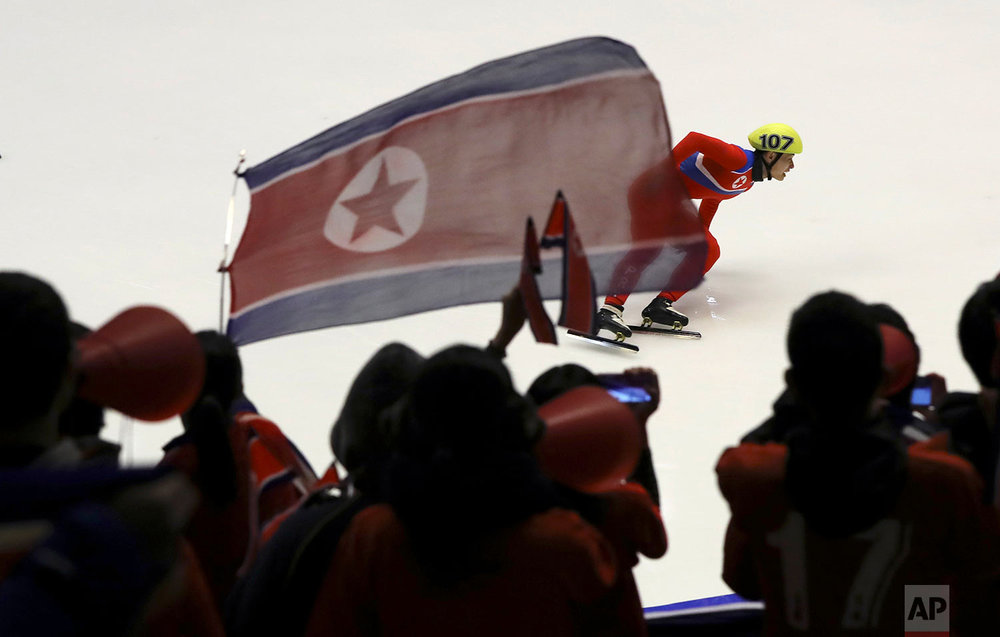 Kim Chol Gwang of North Korea competes as fans of the North Korean team chant during the men's 500 meters heat of short track speed skating competition at the Asian Winter Games at Makomanai Indoor Skating Rink in Sapporo, northern Japan, Tuesday, Feb. 21, 2017. (AP Photo/Eugene Hoshiko)