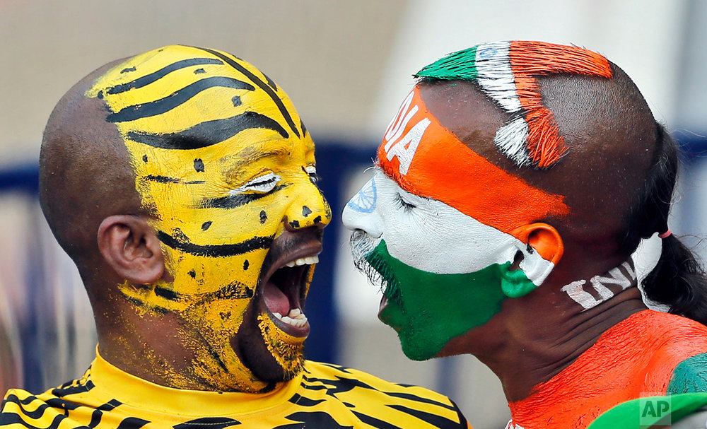 In this Saturday, Feb. 11, 2017 photo, India, right, and Bangladesh cricket fans with faces painted in the colors of their national flags shout to cheer for their teams during the third day of the cricket test match between India and Bangladesh in Hyderabad, India. (AP Photo/Aijaz Rahi)