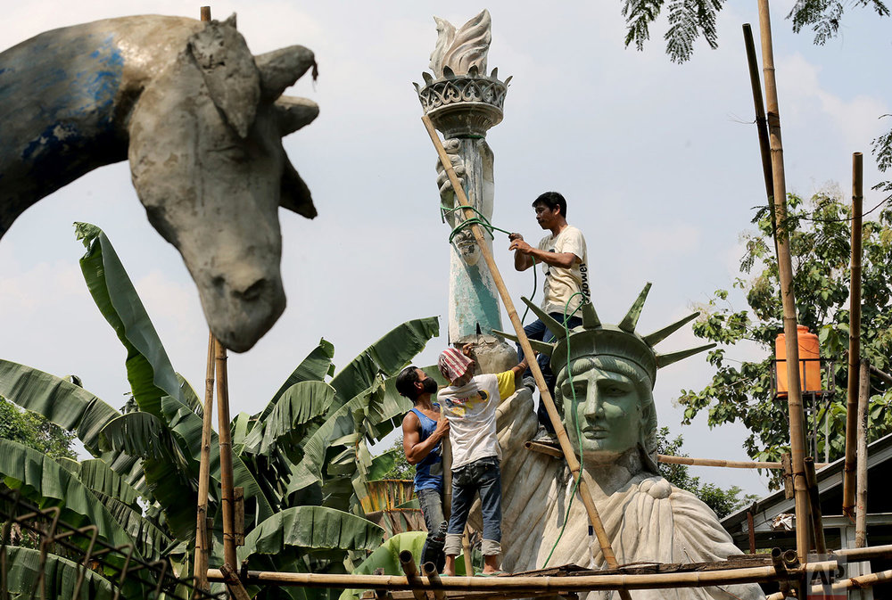 In this Thursday, May 4, 2017, photo, workers build a large replica of the Statue of Liberty at a workshop in Jakarta, Indonesia. The sculpture which costs 170 million Rupiah (U.S $ 17,000) to make will be installed at a public park to attract visitors. (AP Photo/Tatan Syuflana)