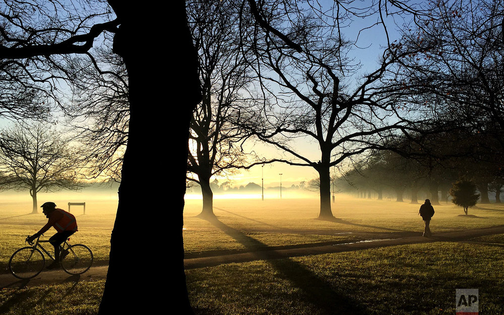 In this Monday, June 26, 2017, file photo, commuters make their way through a mist covered Hagley Park in central Christchurch, New Zealand. Residents of New Zealand's South Island woke to temperatures as low as minus four degrees celsius (28 degrees Fahrenheit) for the start to their working week. (AP Photo/Mark Baker)