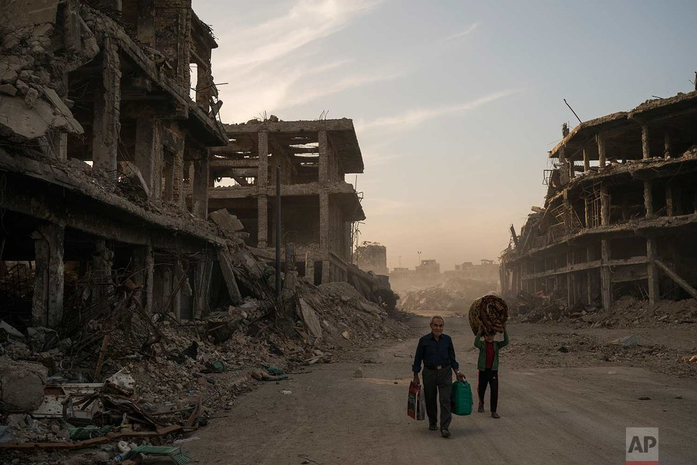 In this Nov. 15, 2017 photo, Haider, left, and Abdullah carry belongings they collected from their damaged house to wash before returning to live in the Old City of Mosul, Iraq. (AP Photo/Felipe Dana)