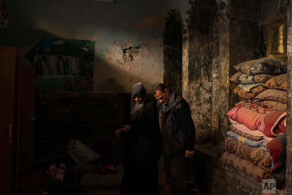 In this Nov. 16, 2017 photo, Yahya Ali, right and Haifa Shehab, look through the rubble in their house in the Old City of Mosul, Iraq. (AP Photo/Felipe Dana)