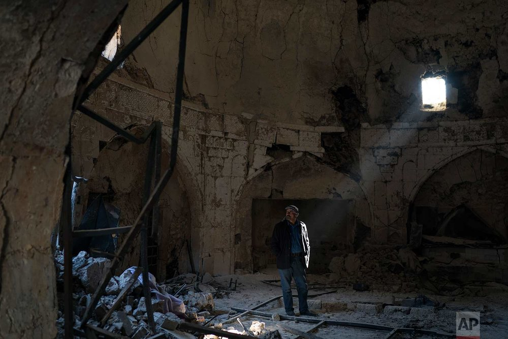 In this Nov. 14, 2017 photo, shop keeper Zyad Mohammed Ali, walks inside a damaged spa in the Old City of Mosul, Iraq. (AP Photo/Felipe Dana)