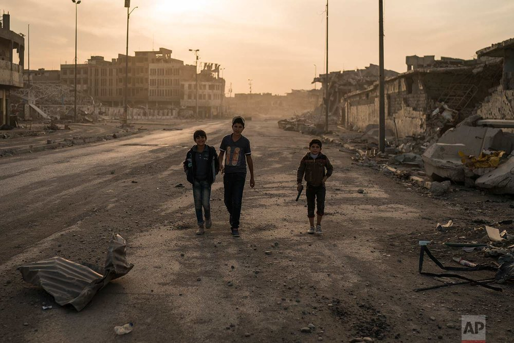 In this Nov. 15, 2017 photo, boys, one of them carrying a toy gun, walk on the empty streets of the Old City, in Mosul, Iraq. (AP Photo/Felipe Dana)