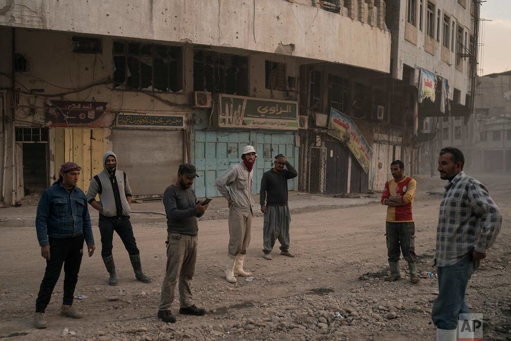 In this Nov. 15, 2017 photo, construction workers gather on a commercial street in the Old City of Mosul, Iraq. (AP Photo/Felipe Dana)