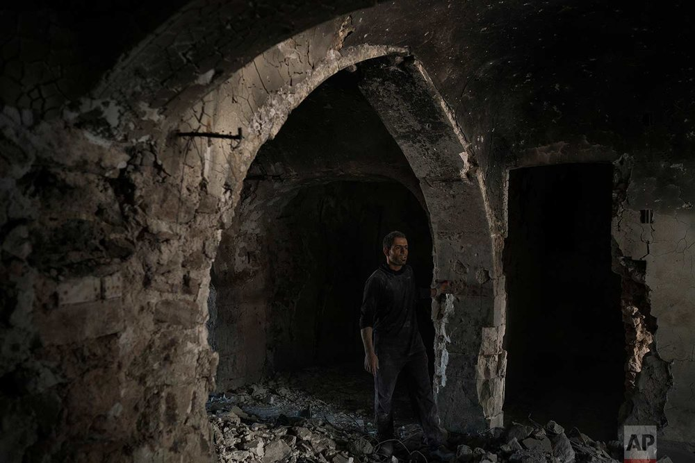 In this Nov. 14, 2017 photo, a construction worker stands in the destroyed old bazaar in the Old City of Mosul, Iraq. (AP Photo/Felipe Dana)