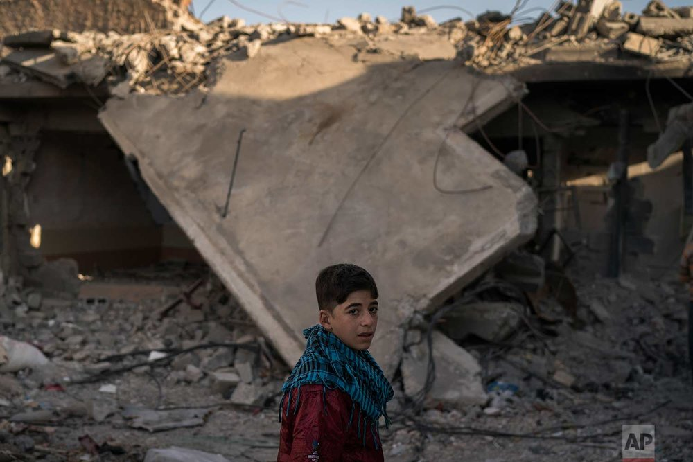 In this Nov. 16, 2017 photo, a boy who recently returned to the Old City walks past a destroyed building near his house in Mosul, Iraq. (AP Photo/Felipe Dana)
