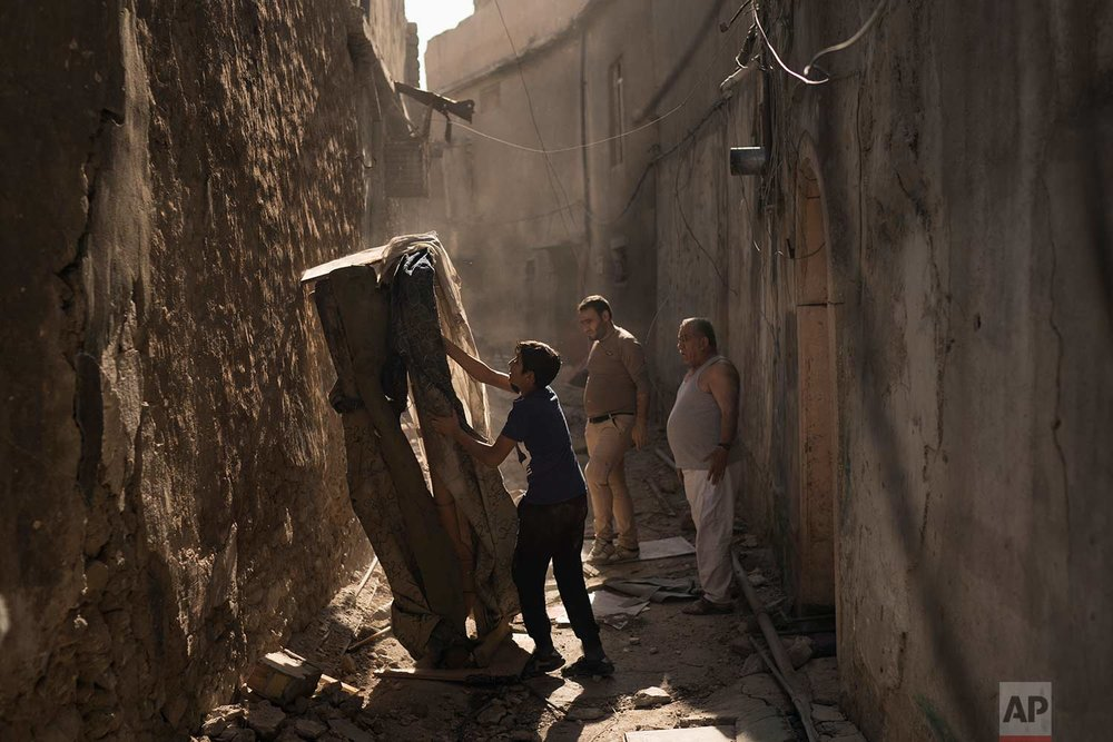 In this Nov. 16, 2017 photo, Mustafa Hansen, left, helps his father Ahmed Mohammed, center, and his grandfather Mohammed Tahar, clear the alley leading to their house in the Old City of Mosul, Iraq. (AP Photo/Felipe Dana)