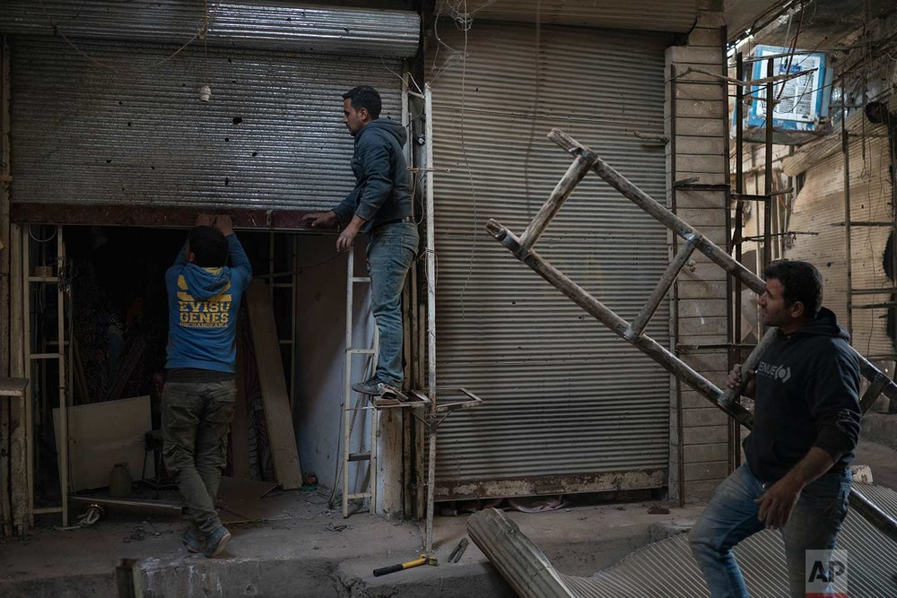In this Nov. 18, 2017 photo, workers repair the door of a shop in the Old City of Mosul, Iraq. (AP Photo/Felipe Dana)