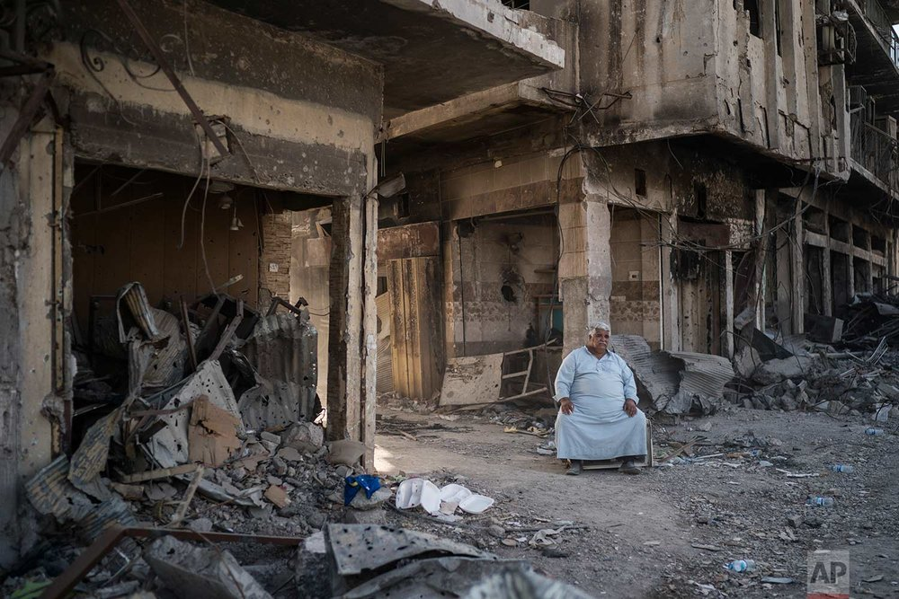 In this Nov. 18, 2017 photo, shop owner Abu Azar sits outside a destroyed bazaar in the Old City of Mosul, Iraq. (AP Photo/Felipe Dana)