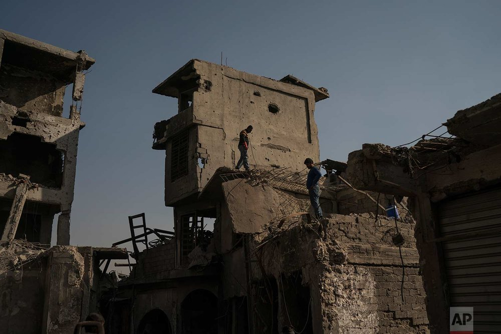 In this Nov. 18, 2017 photo, construction workers stand atop damaged buildings and shops in the Old City of Mosul, Iraq. (AP Photo/Felipe Dana)