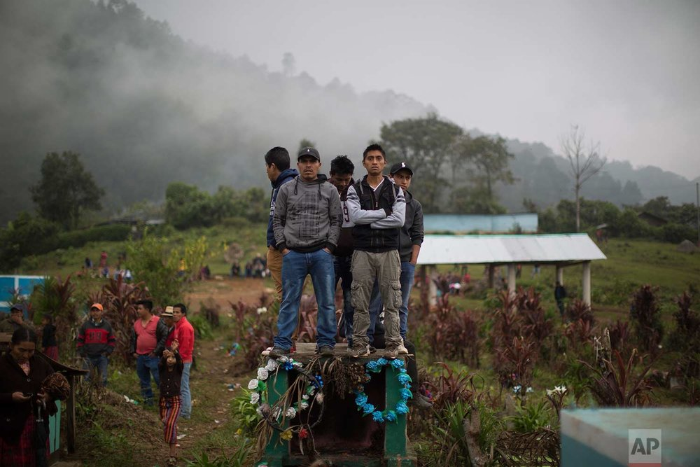 In this Nov. 30, 2017 photo, men stand on a cemetery tomb to get a better view of the burial of 172 Ixil Mayans who died during the civil war, in Santa Avelina, Guatemala. (AP Photo/Luis Soto)