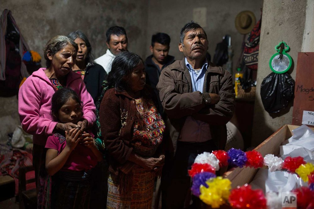 In this Nov. 29, 2017, Baltazar Perez Sanchez, 71, mourns next to the coffin of his mother Magdalena, who died at age 65, during her wake in Santa Avelina, Guatemala. Not seen in the photo are the coffins of two other relatives: Sebastien Perez Mendoza, 32, and Maria Poma Perez, 6. All three were exhumed from a grave in 2014, alongside over 100 other Ixil Mayan who died during the civil war (1978 - 1982). (AP Photo/Luis Soto)