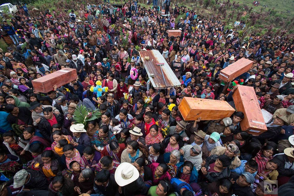 In this Nov. 30, 2017 photo, locals carry the remains of family members who were killed during the civil war, to finally be buried in Santa Avelina, Guatemala. (AP Photo/Luis Soto)