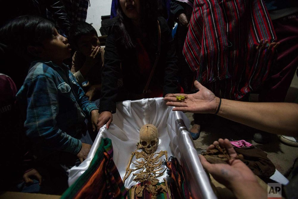 In this Nov. 29, 2017 photo, a forensic anthropologist holds earrings that belonged to 6-year-old Maria Poma Perez, who was exhumed from a mass grave, during her wake in Santa Avelina, Guatemala. The remains of Maria were recognized by her mother when she saw the clothes and earrings, one day before the mass burial of 172 civil war victims, including Maria. (AP Photo/Luis Soto)