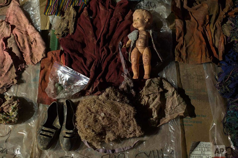 In this Nov. 29, 2017 photo, clothing, earrings and a doll that were found among the remains of over 100 Ixil Mayans exhumed from a mass grave, lay on display for hopeful identification by relatives in Santa Avelina, Guatemala. (AP Photo/Luis Soto)