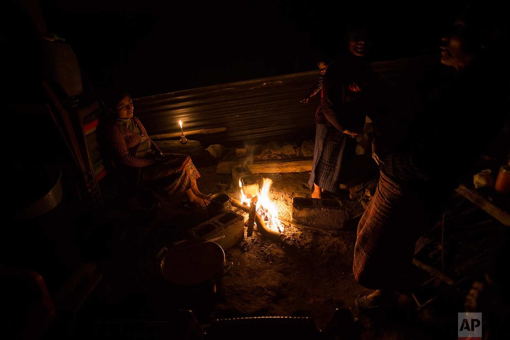 In this Nov. 29, 2017 photo, the relatives of civil war victim Antonio Perez Velasco, whose remains were exhumed and identified, sit around a campfire as they hold a wake for him in Santa Avelina, Guatemala. (AP Photo/Luis Soto)