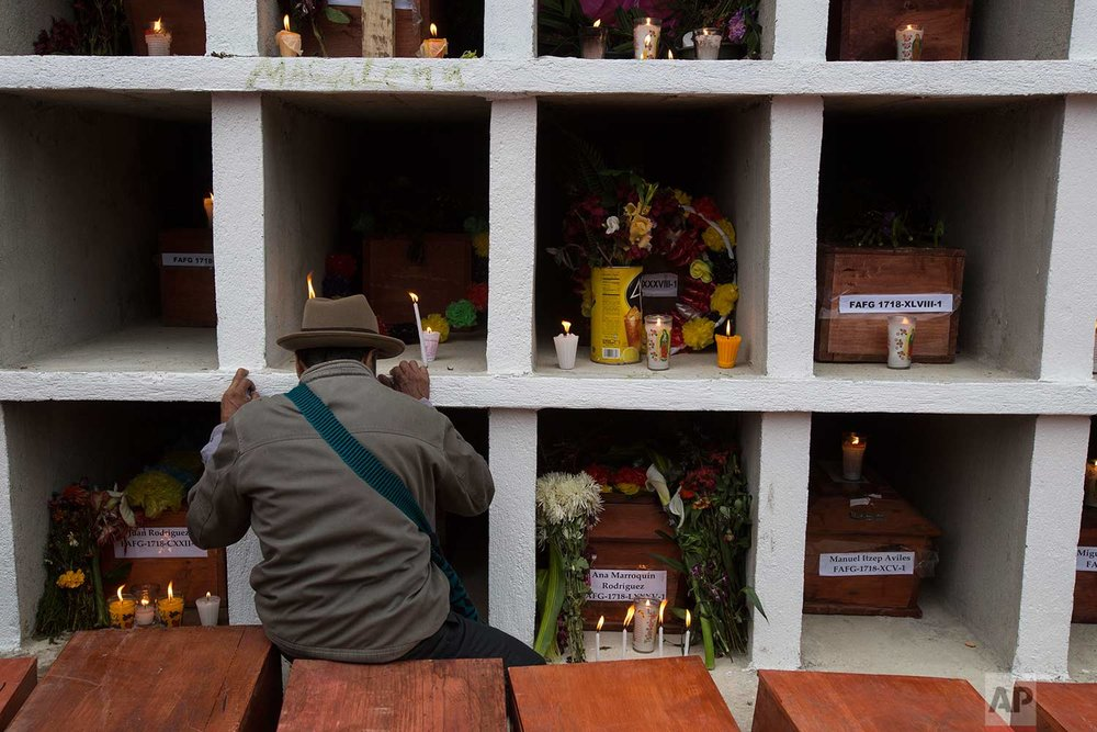 In this Nov. 30, 2017 photo, an Ixil Maya man prays next to the niches where 172 civil war victims were placed, at the cemetery in Santa Avelina, Guatemala. Since the exhumations in Santa Avelina began in 2014, experts have identified 108 of the victims through DNA testing or through personal objects recognized by surviving family members. (AP Photo/Luis Soto)