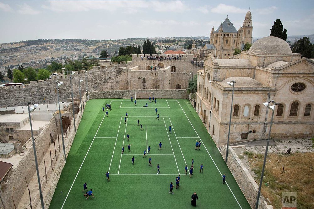 In this Friday, May 19, 2017 photo, Armenian school kids play in the soccer field located next to Jerusalem's Old City Walls at the Sts. Tarkmanchatz Armenian School of Jerusalem. (AP Photo/Oded Balilty)