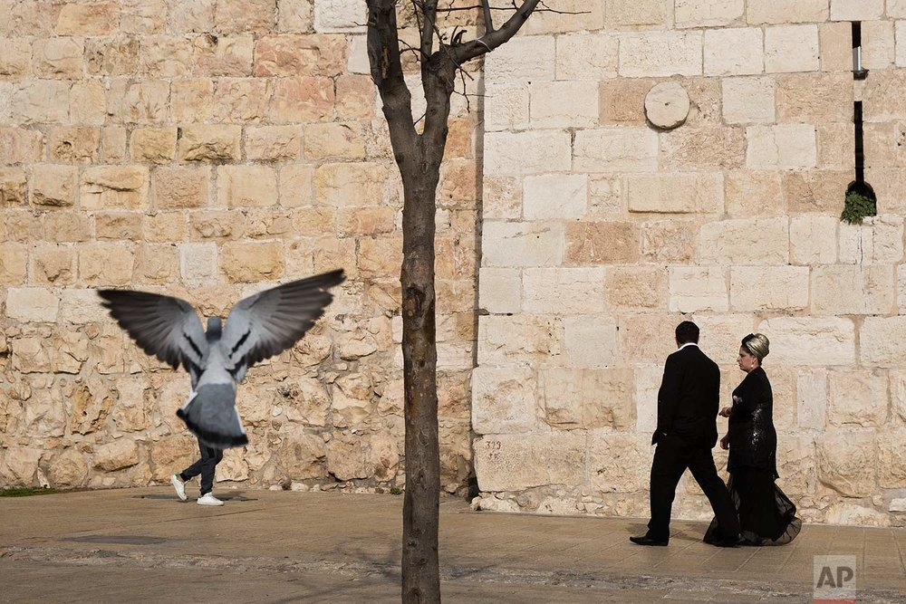 In this Saturday, Dec. 23, 2017 photo, people walk along the Jerusalem's Old City walls, next to Jaffa Gate. (AP Photo/Oded Balilty)