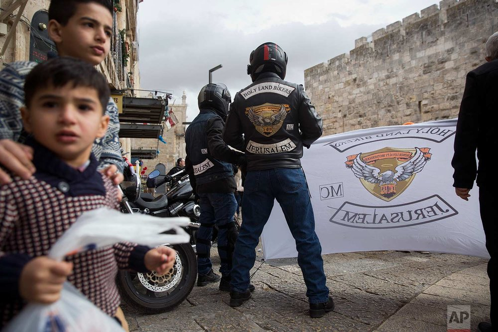 In this Sunday, Dec. 24, 2017 photo, members of Holy Land Bikers group gather in Jerusalem Old City before riding their motorbikes to Bethlehem on Christmas Eve. (AP Photo/Oded Balilty)