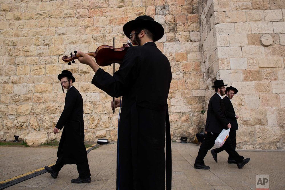 In this Wednesday, Dec. 20, 2017 photo, an ultra-Orthodox Jewish man plays his violin during the Jewish holiday of Hanukkah, at Jaffa Gate in Jerusalem Old City. (AP Photo/Oded Balilty)
