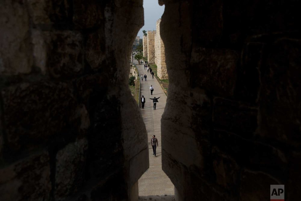 In this Saturday, Dec. 23, 2017 photo, people walk in and out Jerusalem's Old City seen through the Old city walls in Jaffa Gate. (AP Photo/Oded Balilty)