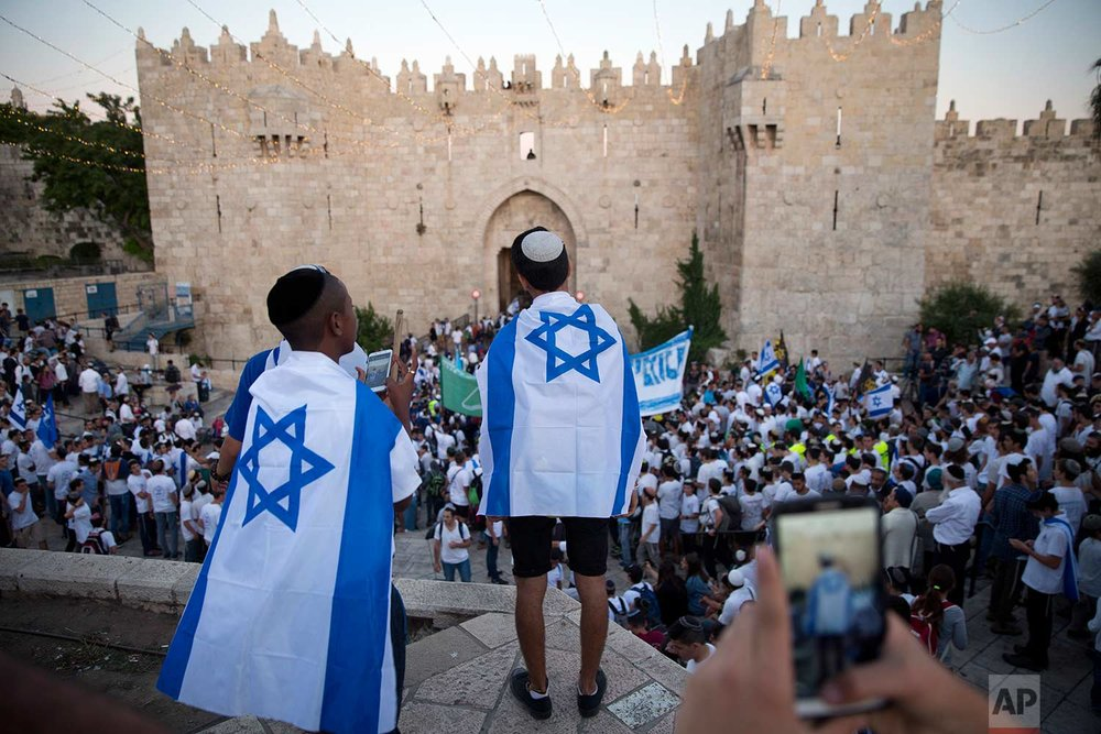 In this Wednesday, May 24, 2017 photo, Israelis carry national flags outside the Old City's Damascus Gate in Jerusalem, during Jerusalem Day which marks the 50th anniversary of Israel's capture of the city's eastern half from Jordanian control during the Six-Day War in 1967. (AP Photo/Oded Balilty)