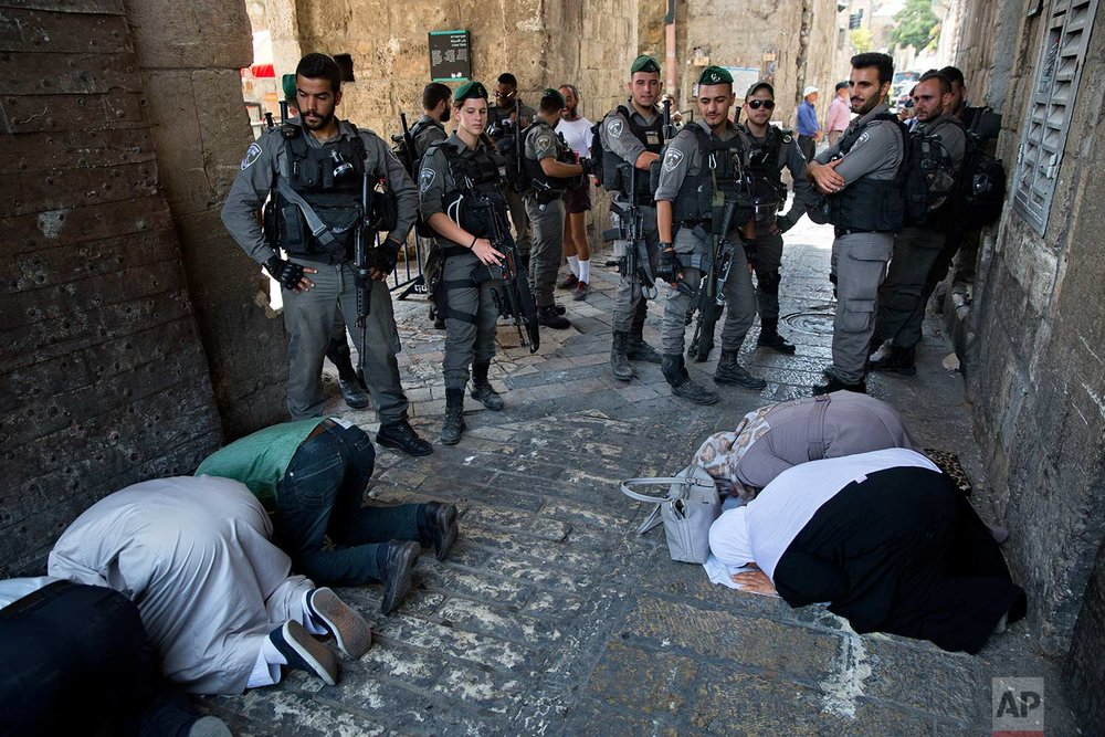 In this Tuesday, July 25, 2017 photo, Palestinians pray as Israeli border police officers stand guard at the Lion's Gate in Jerusalem's Old City. (AP Photo/Oded Balilty)