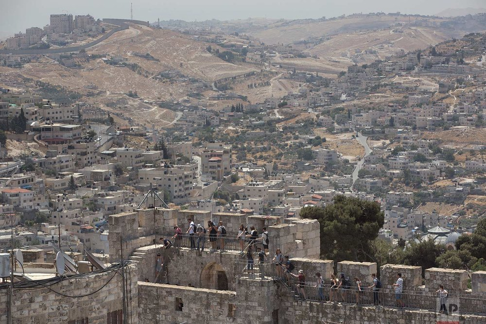 In this Wednesday, May 24, 2017 photo, backdropped by the Silwan neighborhood of east Jerusalem, people tour the Jerusalem Ramparts Walk on Jerusalem's Old City walls. (AP Photo/Oded Balilty)