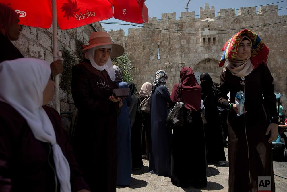 In this Wednesday, July 19, 2017 photo, Palestinians gather for prayer outside the Lion's Gate following an appeal from clerics to pray in the streets instead of inside the Al Aqsa Mosque compound, in Jerusalem's Old City, until a dispute with Israel over security arrangements is settled. (AP Photo/Oded Balilty)