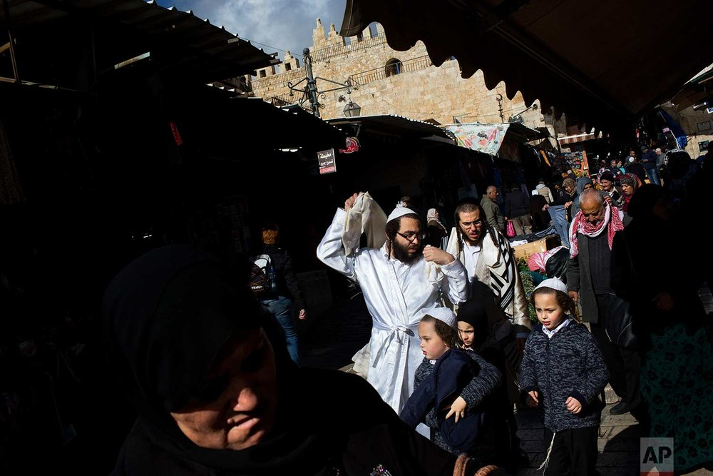 In this Saturday, Dec. 31, 2016 photo, people walk next to Damascus Gate in Jerusalem's Old City, Saturday, Dec. 31, 2016. (AP Photo/Oded Balilty)