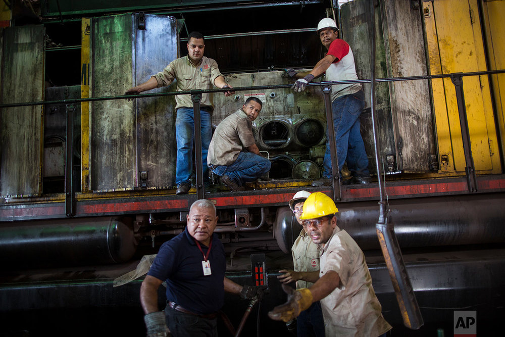 In this Nov. 1, 2017 photo, workers repair a locomotive at Ferrominera Orinoco, in Ciudad Guayana, Bolivar state, Venezuela. In cash-strapped Venezuela, there's no money to buy spare parts. (AP Photo/Rodrigo Abd)