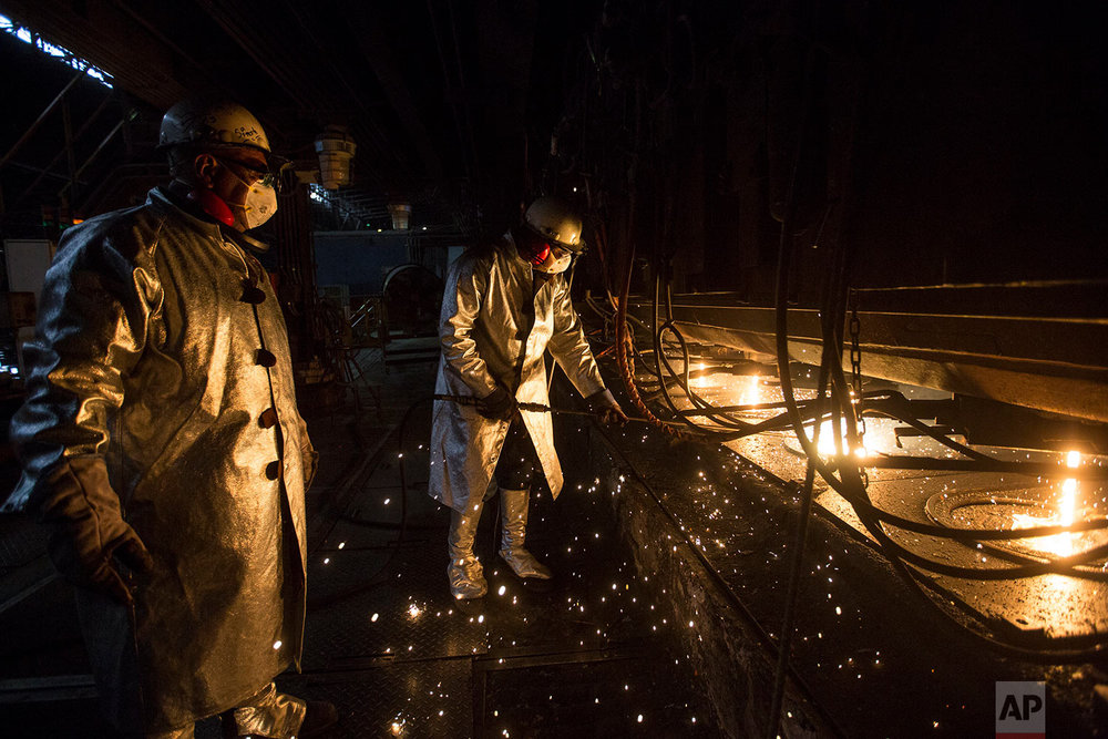 In this Nov. 7, 2017 photo, workers clean the candles, at Sidor's Palanquilla plant, in Ciudad Guayana, Bolivar state, Venezuela. In Sidor, only two of the four smelting ovens that make steel bars are functioning, and workers who used to operate around the clock put in just one shift a day now, officials said. (AP Photo/Rodrigo Abd)