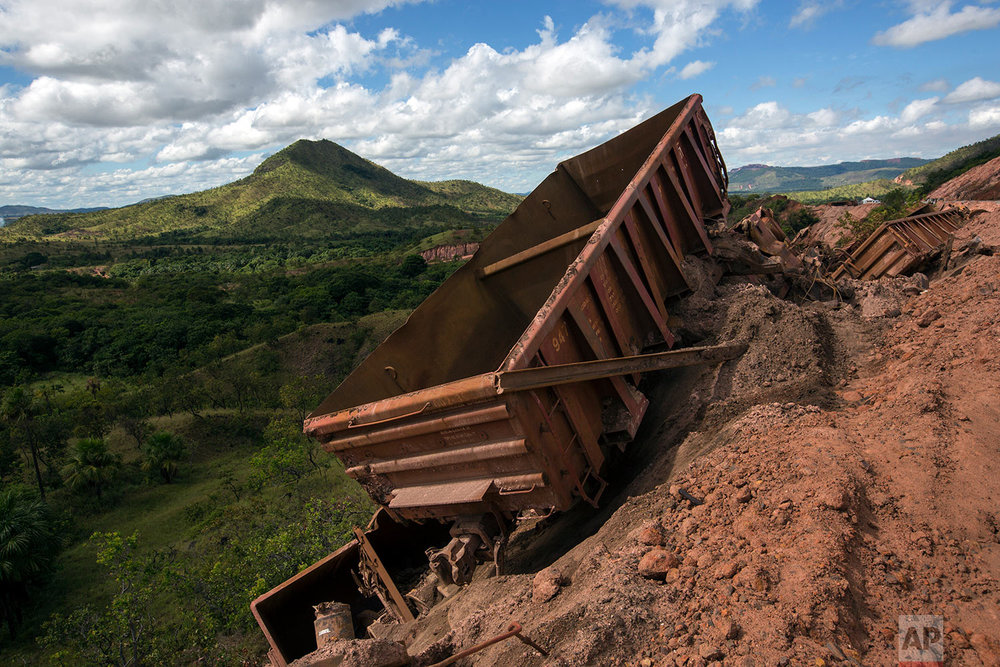 In this Nov. 2, 2017 photo, twisted and derailed wagons that used to carry iron ore lie askew at Ferrominera Orinoco, in Ciudad Piar, Bolivar state, Venezuela. The cars derailed when an engineer was traveling too fast on rails left unmaintained. (AP Photo/Rodrigo Abd)