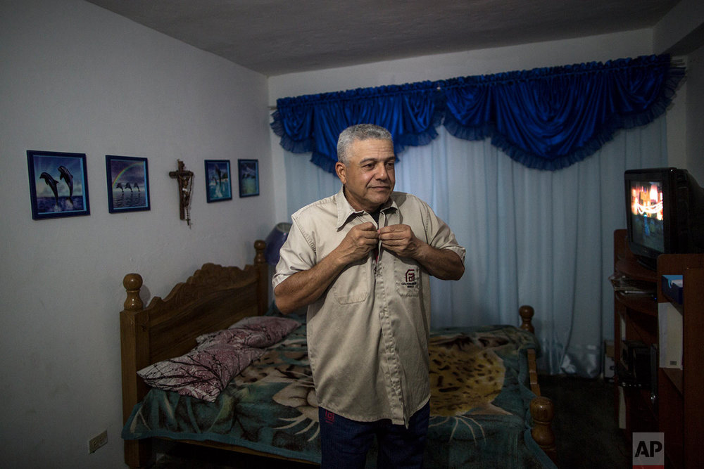 In this Nov. 5, 2017 photo, Tony Franco, who has worked for Ferrominera Orinoco for more than 28 years, puts on his uniform before leaving for the night shift, in Ciudad Guyana, Bolivar state, Venezuela. Franco had to sell his car and now walks several blocks to catch a bus to make it on time for his shift. (AP Photo/Rodrigo Abd)