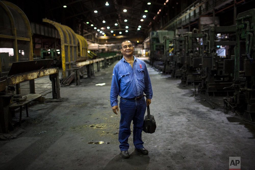 In this Nov. 7, 2017 photo, Cesar Brito poses for a picture inside Sidor's Alambron plant in Ciudad Guayana, Bolivar state, Venezuela. Brito has worked for Sidor for 33 years. (AP Photo/Rodrigo Abd)