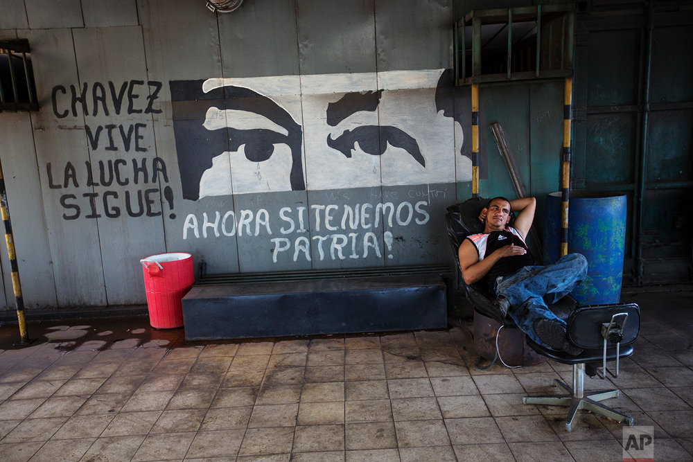 In this Nov. 7, 2017 photo, Jesus Itriago rests after lunch, at the Sidor steel plant, in Ciudad Guayana, Bolivar state, Venezuela. In 2008 Venezuelan President Hugo Chavez began putting the factories, then owned by conglomerates from Japan and Argentina, under the state's control. Output steadily eroded even before the oil price crash. (AP Photo/Rodrigo Abd)