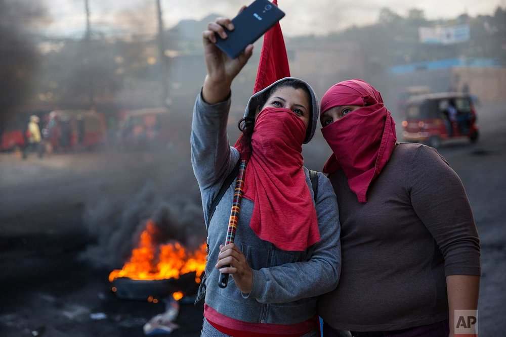 Masked supporters of presidential candidate Salvador Nasralla take a selfie at a burning roadblock set up by demonstrators protesting what they call electoral fraud in Tegucigalpa, Honduras, Friday, Dec. 1, 2017. (AP Photo/Rodrigo Abd)