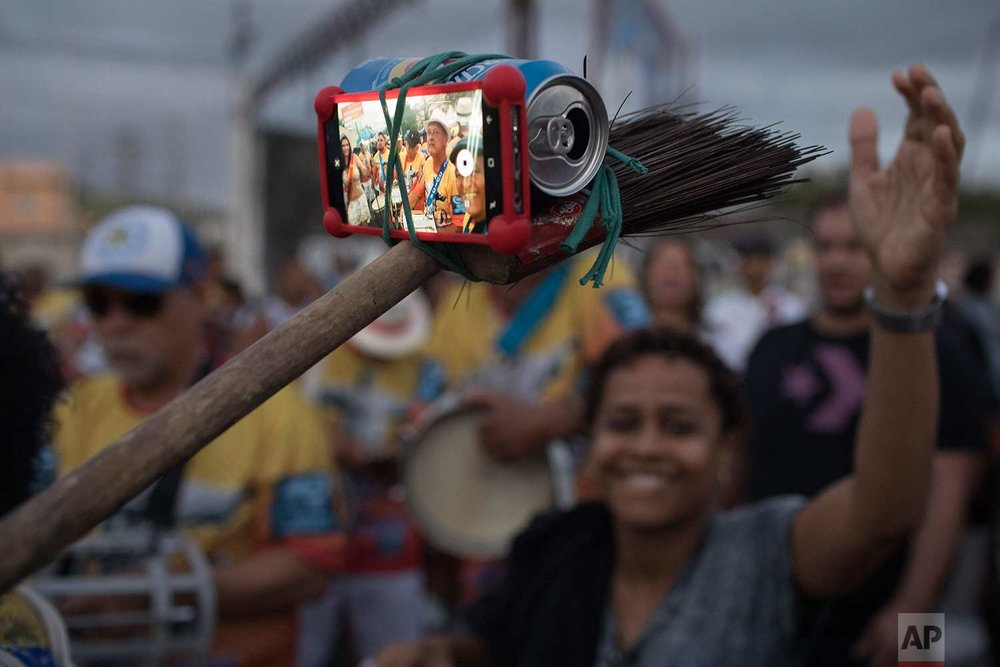 In this Saturday, Dec. 2, 2017 photo, a samba band member turns a broom, beer can and string into a selfie stick at the Oswaldo Cruz neighborhood, marking Samba Day, in Rio de Janeiro, Brazil. (AP Photo/Leo Correa)