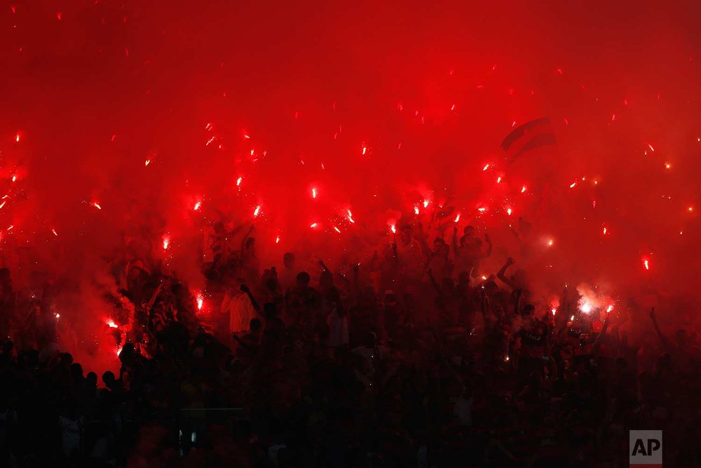 Fans of Brazil's Flamengo soccer team light flares in the stands during a Copa Sudamericana final championship soccer match against Argentina's Independiente at Maracana stadium in Rio de Janeiro, Brazil, Wednesday, Dec.13, 2017. (AP Photo/Silvia Izquierdo)